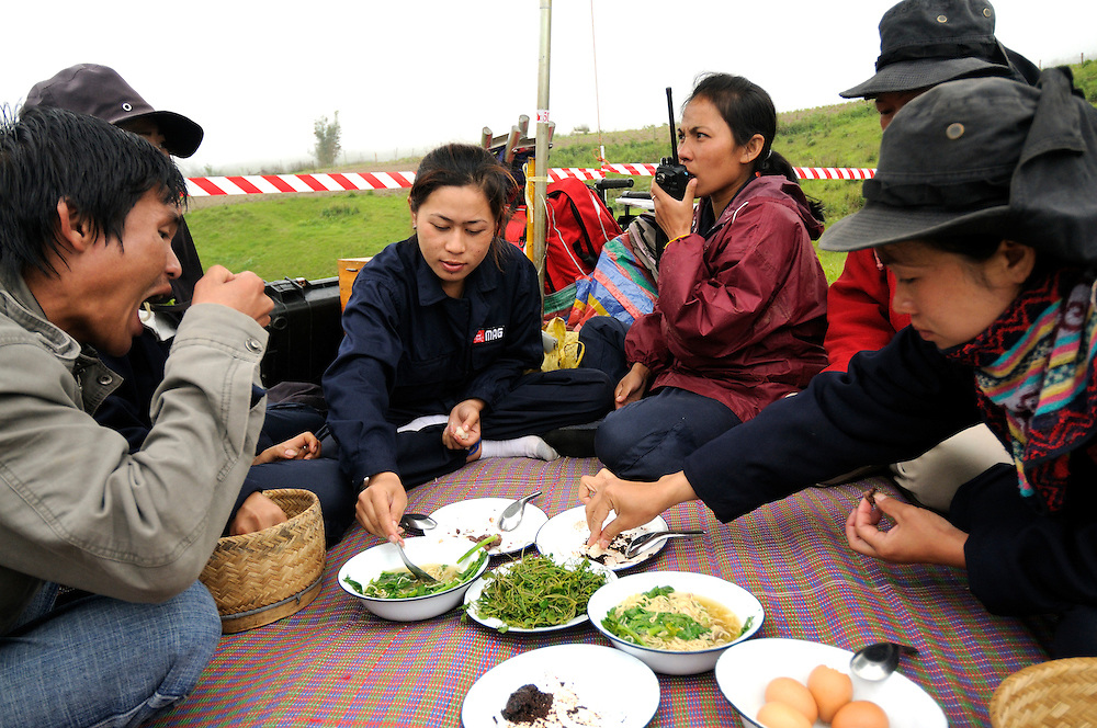 "Part of the ladies team enjoy a lunch of sticky rice, soup, and fresh vegetables, with friends from the regional office. ..Laos was part of a ""Secret War"", waged within its borders primarily by the USA and North Vietnam.  Many left over weapons supplied by China and Russia continue to kill.  However, between 90 and 270 million fist size cluster bombs were dropped on Laos by the USA, with a failure rate up to 30%.  Millions of live cluster bombs still contaminate large areas of Laos causing death and injury..The US Military dropped approximately 2 million tons of bombs on Laos making it, per capita, the most heavily bombed country in the world.   ..The women of Mines Advisory Group (MAG) work everyday under dangerous conditions removing unexploded ordinance (UXO) from fields and villages...***All photographs of MAG's work must include (either on the photo or right next to it) the credit as follows:  Mine clearance by MAG (Reg. charity)***."