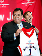 Governor Chris Christie jokes that a jersey presented to him by Special Olympians including Robert Fredericks, right,  will not be the right size to fit him.