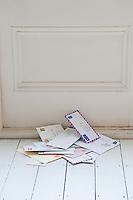 Letters on floorboards at front door