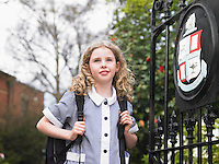 Elementary schoolgirl standing by school gate