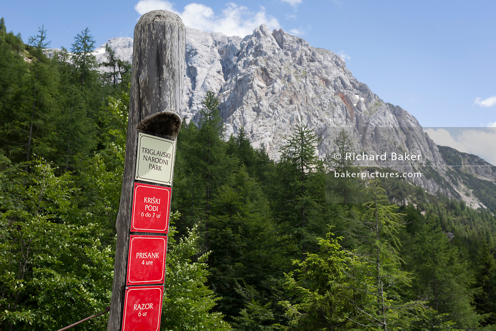 Hiking trail markers beneath the Prisank (2547m) mountain view at the top of Vrsic Pass in the Slovenian Julian Alps, on 22nd June 2018, in Triglav National Park, Slovenia.