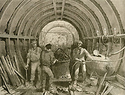 'Tunnelling work in progress on the expanding London underground railway system, showing men in section of lined tunnel lit by candles.  Engraving, 1888.'
