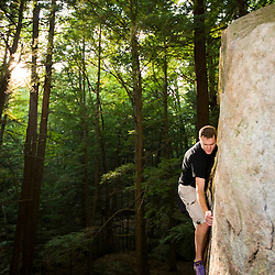 "A man bouldering in ""The Boulders"" section of New Hampshire's Pawtuckaway State Park."