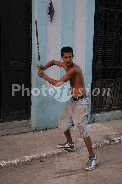 Young man playing baseball in Havana backstreet,