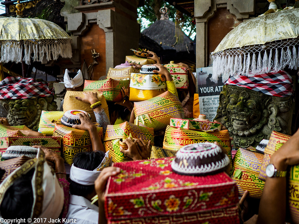 """02 AUGUST 2017 - UBUD, BALI, INDONESIA: Women file into the temple during the """"Merchants' Day"""" ceremony at the Pura (Temple) Melanting Pasar Ubud, the small Hindu temple in the Ubud market. It's a day that merchants throughout Ubud come to the temple to make offerings and pray for prosperity.    PHOTO BY JACK KURTZ"""