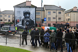 © London News Pictures. 21/03/2017. Derry, UK. A coffin carrying the body of Martin McGuinness makes its way though the nationalist Bogside area of Derry, Northern Ireland, 21 March 2017. Sinn Féin's Martin McGuinness, Northern Ireland's former deputy first minister died aged 66 early this morning. It is understood he had been suffering from a rare heart condition. The former IRA leader turned peacemaker worked at the heart of the power-sharing government following the 1998 Good Friday Agreement. He became deputy first minister in 2007, standing alongside Democratic Unionist Party leaders Ian Paisley, Peter Robinson and Arlene Foster.. Photo credit: LNP