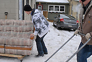 A man moves a sofa and another man plows snow from the parking lot of Worth a Second Look in Kitchener, Ontario, Canada. Both men work under Job Cafe, a program of The Working Centre.