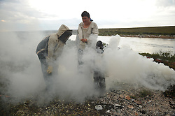Dene First Nation youth Brendan Felix Head, 14, left, Tristen Jade Lockhart, 14, center and Hawke Williams Ellis, 4, stand in the smoke to get relief form the carnage of millions of black flies and mosquitoes. (Photo by Ami Vitale)