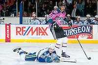 KELOWNA, CANADA - OCTOBER 15: Riley Stotts #12 of Swift Current Broncos falls to the ice after a hit by Braydyn Chizen #22 of Kelowna Rockets on October 15, 2016 at Prospera Place in Kelowna, British Columbia, Canada.  (Photo by Marissa Baecker/Shoot the Breeze)  *** Local Caption *** Braydyn Chizen;