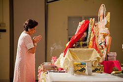 Nita Sakhrani offers prayers at the feet of Ganesha.  The India Association of the Virgin Islands celebrates the end of Ganesha Chaturthi the ten day Hindu festival to honor the elephant-headed god Ganesha.  During the festival adherents chant and sing songs of worship, present offerings of fruit and flowers,  and whisper prayers and wishes to the god.  India Association of the Virgin Islands Culture Center.  Frenchman's Bay.  St. Thomas.  15 September 2016.  © Aisha-Zakiya Boyd
