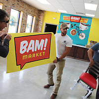 From left, Jeff, Colby and Perry Knowles organize the interior of BAM! Market, which is currently under construction alongside Highway 45 in Nettleton.