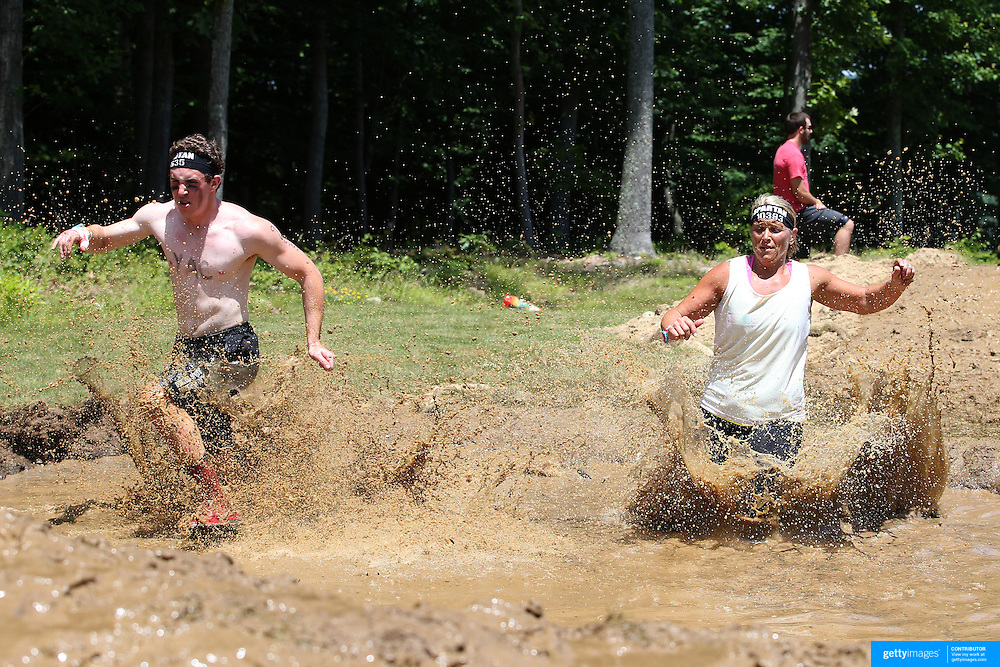 Competitors in action at the mud and water obstacle during the Reebok Spartan Race. Mohegan Sun, Uncasville, Connecticut, USA. 28th June 2014. Photo Tim Clayton
