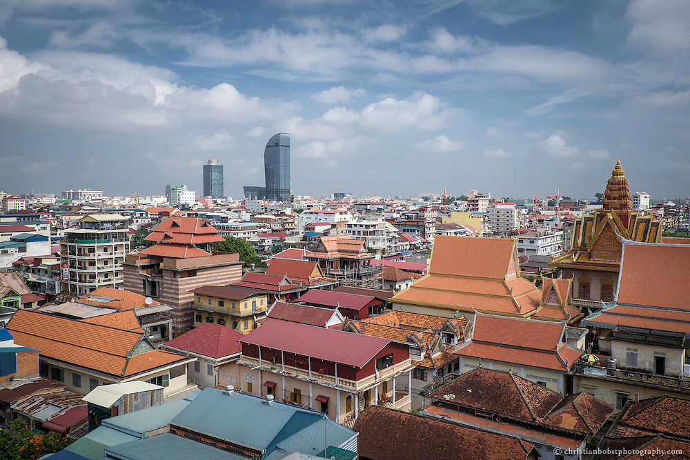 View of the rooftop patio of the Frangipani royal Palace hotel & spa on the roofs of Phnom Penh. In the foreground, on the right, one can see the orange roofs of the Wat Ounalom temple arrangement. In the background, the freshly finished 188 meters high Vattac Capital Tower dominates the skyline.