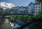The Water of Leith river flows through Dean Village, the site of old watermills in a deep gorge, in Edinburgh, the capital city of Scotland, in Lothian on the Firth of Forth, Scotland, United Kingdom, Europe. This image was stitched from several overlapping photos.