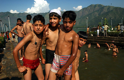 KASHMIR,INDIA, JULY 25:  Kashmiri children enjoy some relief from the scalding temperatures with a swim in Dal Lake at the base of the Himalayas in Srinagar, the Indian held summer capital of the state of Jammu and Kashmir July 25, 2003.  Islamic guerrillas have been fighting for independence of the Indian-controlled portion of Kashmir since 1989 but for the first time in 13 years, Kashmiris living in Srinagar have enjoyed a fragile peace and rise in tourism.