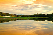 Landscape image of goolf course with orange sunlught and reflected clouds