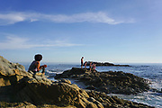 Tourists on the Rocks along the Coastline of Laguna Beach
