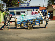 "15 FEBRUARY 2016 - ARANYAPRATHET, SA KAEO, THAILAND: Cambodian porters in Aranyaprathet pull a load of bottled water to the Cambodian side of the border. Thais selling bottled water in the border town of Aranyaprathet, opposite Poipet, Cambodia, have reported a surge in sales recently. Cambodian officials told their Thai counterparts that because of the 2016 drought, which is affecting Thailand and Cambodia, there have been spot shortages of drinking water near the Thai-Cambodian and that ""water shortages in Cambodia had prompted people to hoard drinking water from Thailand.""     PHOTO BY JACK KURTZ"