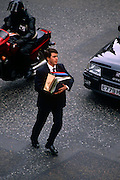 An office worker dashes across a road in the City of London, narrowly avoiding a motorbike and car in his urgency to get across to a meeting with associates with his armful of paperwork in files and ring binders. His safety far outweighs the risks of colliding with traffic.