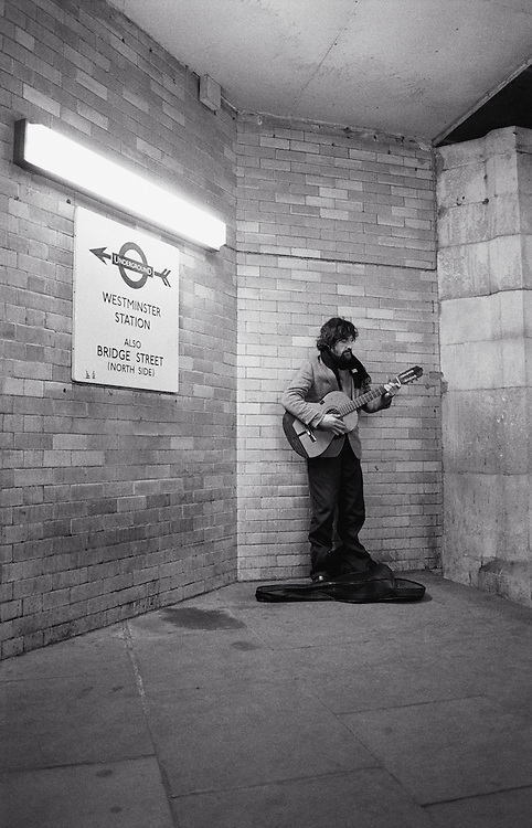 Man playing guitar in entrance to Westminster Station