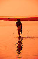 A man walks along a beach against a background of orange.  Bali, Indonesia.