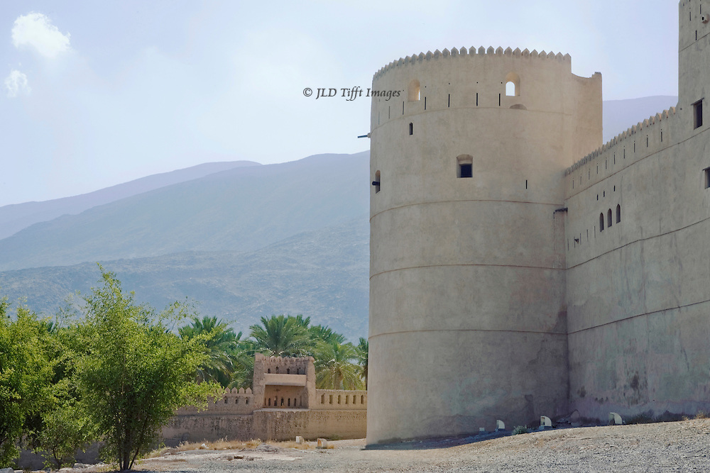 Al Rustaq Fort, at the foot of Al Jabal Al Akhdar on the edge of the Batinah Plain, Oman. Originally constructed circa 1250 AD on Persian ruins from the 7th century AD, The imposing present-day structure was rebuilt by the first ruler of the Ya'ruba dynasty in 1650.   Rustaq has long been important because of its strategic situation at the openings of mountain passes, as well as its benign climate and hot springs, which are believed to have medicinal benefits. It was the site in 1624 of the election of the first imam of the Ya'ariba, Nasir bin Murshid bin Sultan, and served as the imamate's capital a number of times, controlling trade between Oman's coastal ports and the mountainous interior.