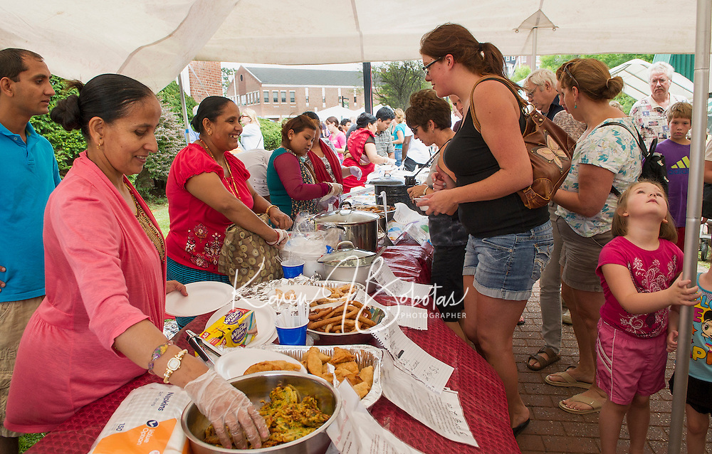 Saraswati Tinsina and Madhabi Dahal prepare an array of Bhutanese specialties during prior Multicultural Day festivities in downtown Laconia.  (Karen Bobotas/for the Laconia Daily Sun)