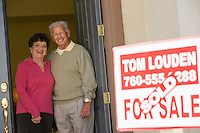 Senior couple standing in doorway of their new home