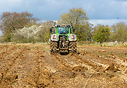 Tractor turning over soil in spring to prepare for cultivation, Sutton, Suffolk, England, UK