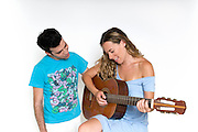A young couple in their 20s sharing an intimate moment, playing a guitar and singing together on a white background Model Releases available
