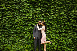 Woman Kissing Man on Cheek in front of Green Leafy Hedge