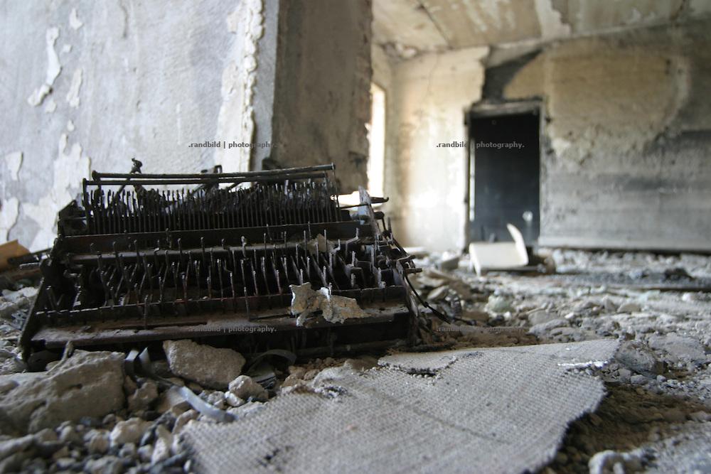 Georgien/Abchasien, Suchumi, 2006-09-02, Eine verbrannte Schreibmaschine im kriegszerstörten Parlamentsgebäude in Suchumi. Abchasien erklärte sich 1992 unabhängig von Georgien. Nach einem einjährigen blutigen Krieg zwischen den Abchasen und Georgiern besteht seit 1994 ein brüchiger Waffenstillstand, der von einer UNO-Beobachtermission unter personeller Beteiligung Deutschlands überwacht wird. Trotzdem gibt es, vor allem im Kodorital immer wieder bewaffnete Auseinandersetzungen zwischen den Armee der Länder sowie irregulären Kämpfern. (A burned typewriter in an office of the war destroyed parliament building in Sokhumi. Abkhazia declared itself independent from Georgia in 1992. After a bloody civil war a UNO mission observing the ceasefire line between Georgia and Abkhazia since 1994. Nevertheless nearly every day armed incidents take place in the Kodori gorge between the both armys and unregular fighters )