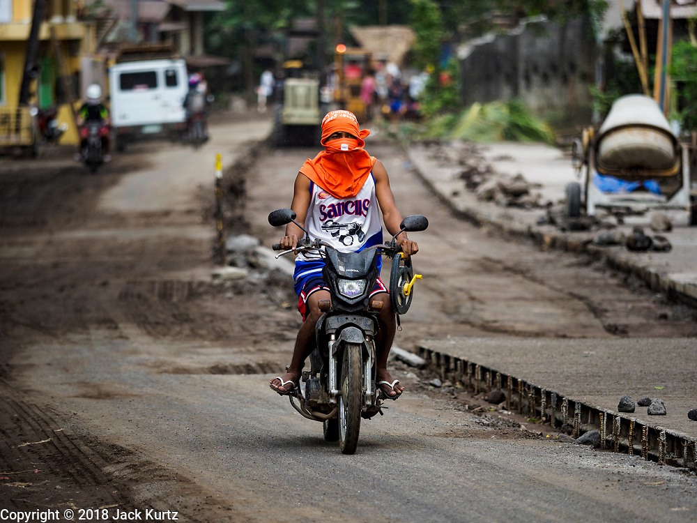 """22 JANUARY 2018 - GUINOBATAN, ALBAY, PHILIPPINES: A man on a motorcycle in Guinobatan wears a face mask while he drives through the community. Several communities in Guinobatan were hit ash falls from the eruptions of the Mayon volcano and many people wore face masks to protect themselves from the ash. There were a series of eruptions on the Mayon volcano near Legazpi Monday. The eruptions started Sunday night and continued through the day. At about midday the volcano sent a plume of ash and smoke towering over Camalig, the largest municipality near the volcano. The Philippine Institute of Volcanology and Seismology (PHIVOLCS) extended the six kilometer danger zone to eight kilometers and raised the alert level from three to four. This is the first time the alert level has been at four since 2009. A level four alert means a """"Hazardous Eruption is Imminent"""" and there is """"intense unrest"""" in the volcano. The Mayon volcano is the most active volcano in the Philippines. Sunday and Monday's eruptions caused ash falls in several communities but there were no known injuries.    PHOTO BY JACK KURTZ"""