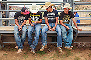 14 JULY 2012 - OAK SPRINGS, AZ:  Cowboys look at a smart phone after a bull riding class at the Aspen Canyon Rodeo Club in Oak Springs, AZ. The bull riding class was offered by the Crooked Horn Cattle Co. in the community of Oak Springs on the Navajo Nation, about 15 miles south of Window Rock, AZ. Eleven cowboys signed up for bull riding classes and one signed up for bull fighting classes. The bull riding class started with lessons on a mechanical bucking machine before the cowboys rode bulls.    PHOTO BY JACK KURTZ