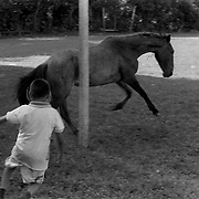 Fabian, 10, chases a horse off the field where he and friends were playing soccer on the Maleku reservation.