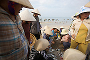 Hundreds of trawlers assembled at the fishing harbour. Women with traditional cone hats trading and selling fresh fish.