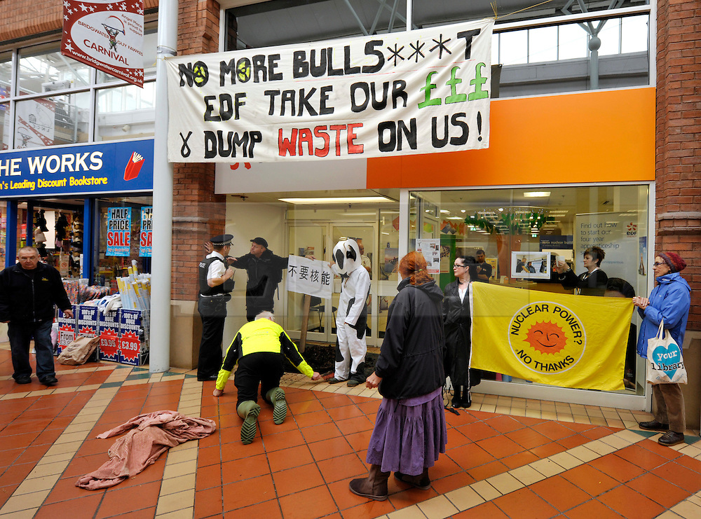 """© Licensed to London News Pictures. 21/10/2013.  Bridgwater, Somerset, UK.  Anti-nuclear protesters hang a banner and dump manure at the EDF Energy shop in Angel Place shopping centre in Bridgwater, with a sign in Chinese lettering which they say means """"No Nuclear Power"""".  The UK Government today announced the go-ahead for a new nuclear power station at Hinkley Point C in Somerset, to be built by a consortium with French firm EDF Energy and Chinese investment for the first time in UK nuclear power generation.  A kneeling protester is clearing the manure off the main concourse of the shopping centre. 21October 2013.<br /> Photo credit : Simon Chapman/LNP"""