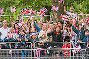 Excited fans wave Union Jacks - Queens 90th birthday was celebrated by the traditional Trooping the Colour as well as a flotilla on the river Thames.