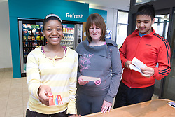 Group of adults checking in at the reception desk of their sports leisure centre,