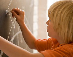 Young boy writing on a blackboard