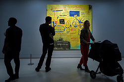 "© Licensed to London News Pictures. 20/09/2017. London, UK. Visitors view ""Hollywood Africans"", 1983, by Jean-Michel Basquiat. Preview of ""Basquiat: Boom for Real"", the first large-scale exhibition in the UK of the work of American artist Jean-Michel Basquiat (1960-1988) taking place at the Barbican Art Gallery, 21 September-28 January 2018. Photo credit : Stephen Chung/LNP"