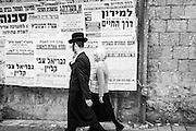 A young married couple of religious Jews walks on Me'A  She'arim Street in Jerusalem on a Tuesday afternoon. The short hat worned by the man and the hancarchif worned by the woman identify them, most likely, as decendent from one of the largest orthodox dynasty existing, the Satmar, from Hungary.