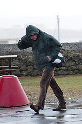 © London News Pictures. 08/02/2014. Porthcawl,UK. A man struggles through gale force winds in Porthcawl, Wales. Photo credit : Graham M. Lawrence/LNP.