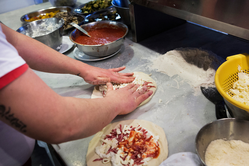 NAPLES, ITALY - 12 DECEMBER 2014: A pizza is prepared at the Pizzeria Oliva da Concettina ai Tre Santi (where customers can offer &quot;suspended pizzas&quot;), in the Sanit&agrave; district in Naples, Italy, on December 12th 2014.<br /> <br /> The suspended pizzas derives from the tradition of the caff&egrave; sospeso,or suspended coffee. The suspended coffee is a cup of coffee paid for in advance as an anonymous act of charity. The tradition began in the working-class caf&eacute;s of Naples, where someone would order a sospeso, paying the price of two coffees but receiving and consuming only one. A poor person enquiring later whether there was a sospeso available would then be served a coffee for free. &quot;suspended pizzas&quot;), in the Sanit&agrave; district in Naples, Italy, on December 12th 2014.<br /> <br /> The suspended pizzas derives from the tradition of the caff&egrave; sospeso,or suspended coffee. The suspended coffee is a cup of coffee paid for in advance as an anonymous act of charity. The tradition began in the working-class caf&eacute;s of Naples, where someone would order a sospeso, paying the price of two coffees but receiving and consuming only one. A poor person enquiring later whether there was a sospeso available would then be served a coffee for free.