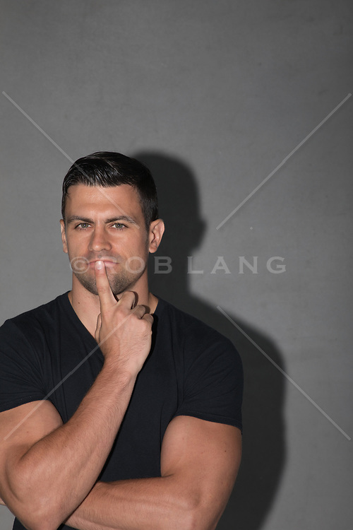 studio portrait of a handsome 30 something man with black hair and green eyes