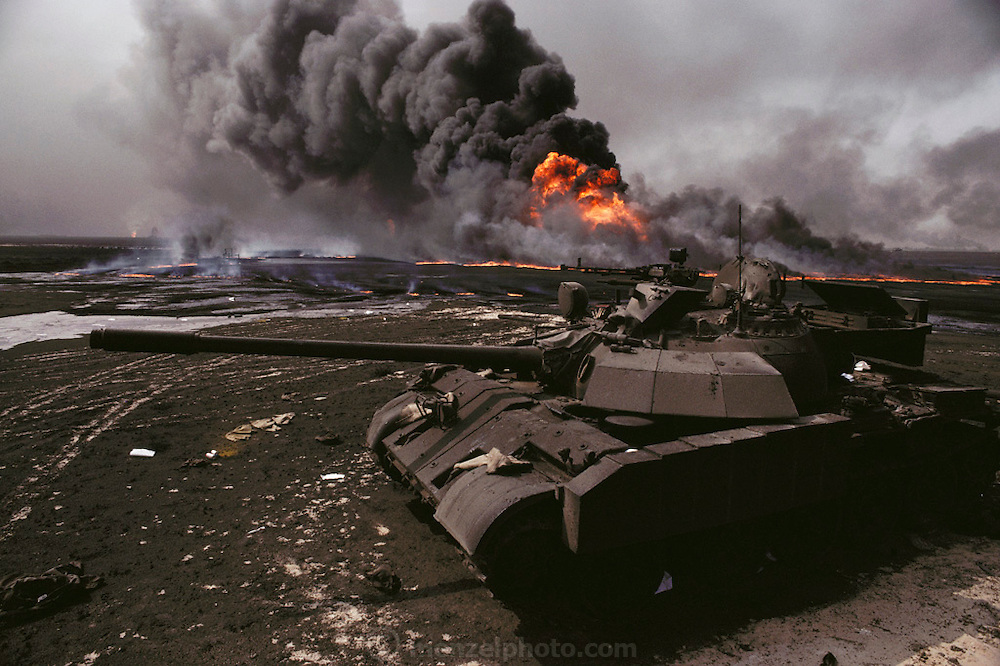An abandoned Iraqi tank in front of the burning Magwa oil fields in Kuwait after the end of the Gulf War in 1991 (July, 1991). The desert was covered in oil that rained down from the clouds of oil smoke and oil shooting into the air after a fire had been extinguished. More than 700 wells were set ablaze by retreating Iraqi troops creating the largest man-made environmental disaster in history.
