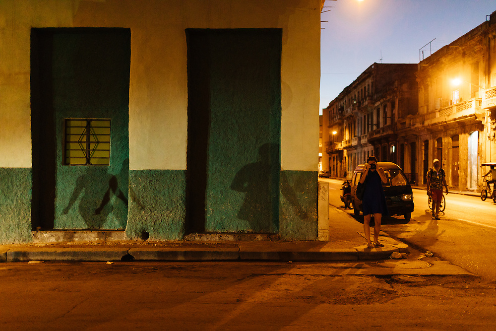 20 something girl takes photograph as the sun sets and the streetlights come on in Old Havana, Havana Cuba