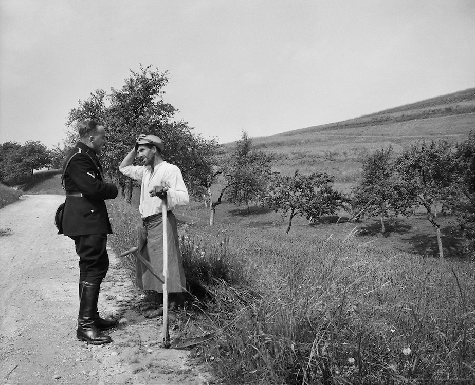 Farmworker with Schythe Talking with SS Officer, Aschach Valley, Mühlviertel, Upper Austria, 1938