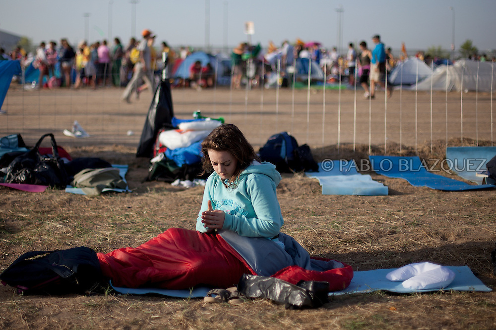 A pilgrim wait for Pope Pope Benedict XVI at the base of Cuatro Vientos, eight kilometres (five miles) southwest of Madrid on August 21, 2011.The pilgrims spent the night in the open air at the base of Cuatro Vientos, eight kilometres (five miles) southwest of Madrid, where Pope Benedict XVI celebrates the closing mass of the August 16-21 youth festival on Sunday morning