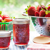 Fresh strawberries in a stainless steel colander and strawberry jam in glass jam jars sitting on a blue and white checkered cloth against a fresh, sunny green background.